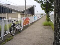 タコやイカ、カニなどの絵が描かれた歩道横の柵の写真です。